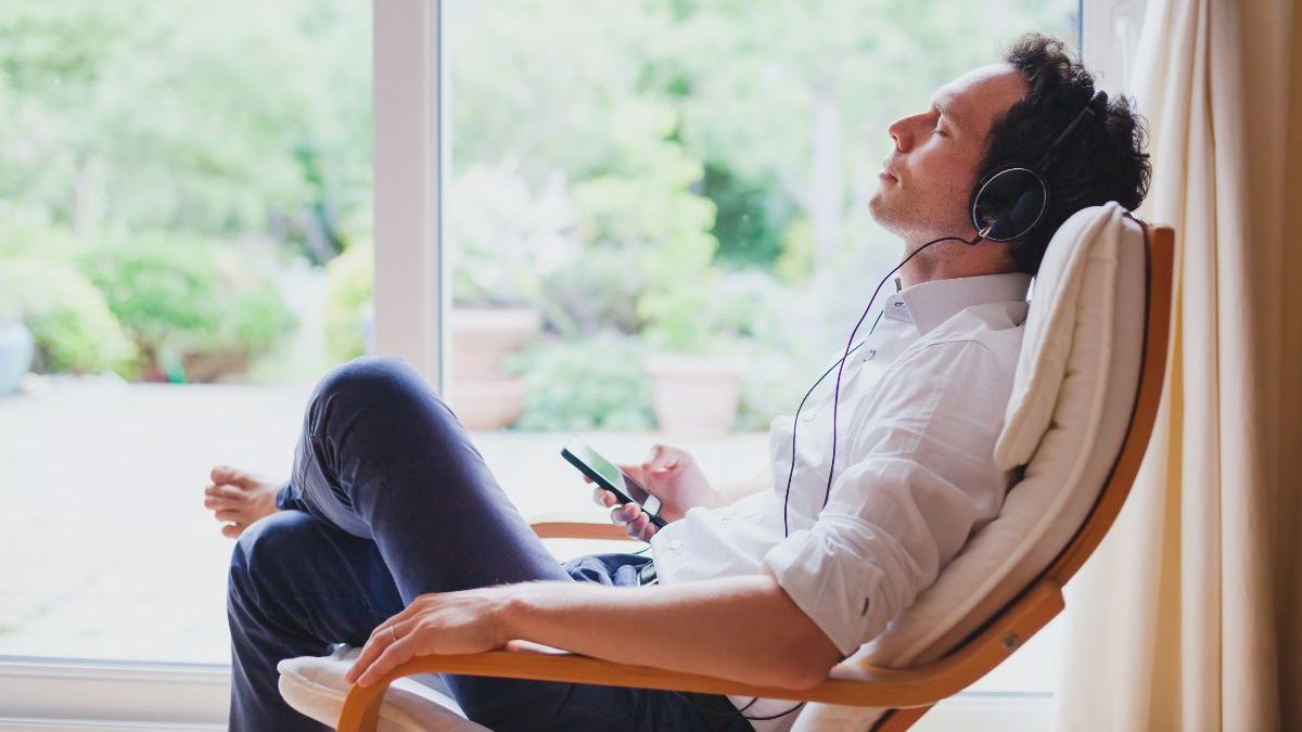 Man reclining and listening to music through headphones