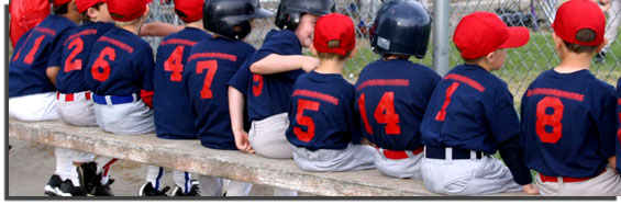young boys in baseball uniforms sitting on the bench