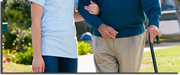 Man with a cane leaning on a physical therapist