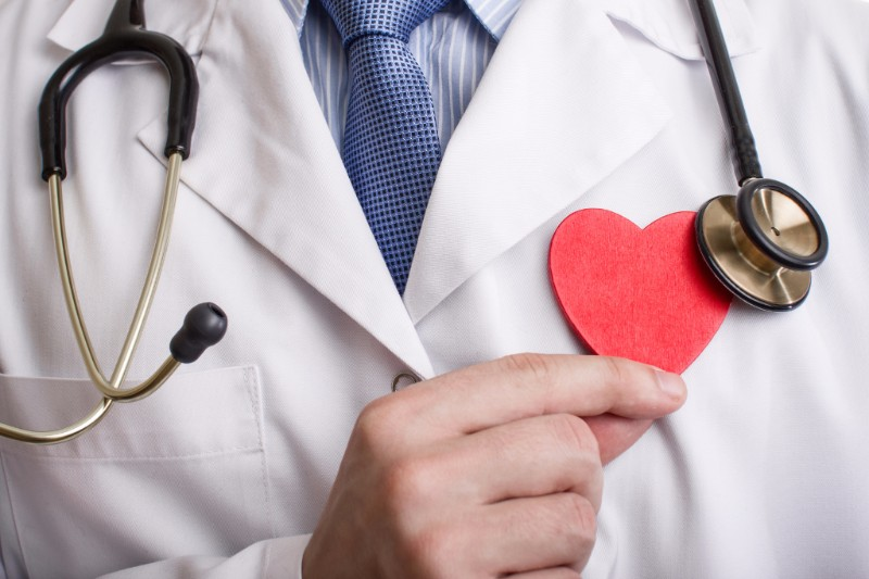 doctor holding a red paper heart over his chest