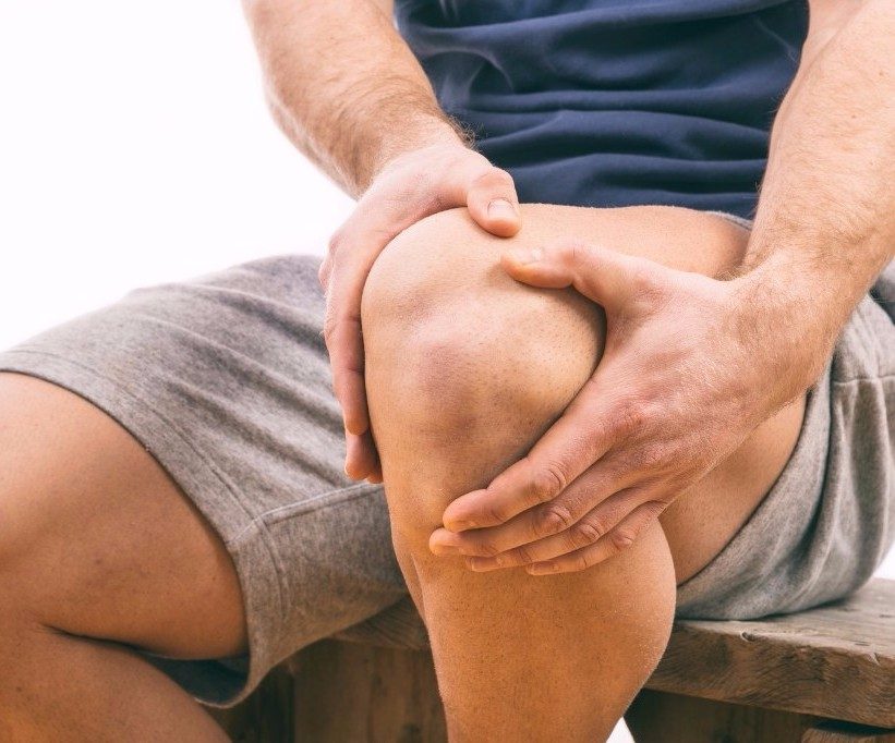 Man gripping knee in pain